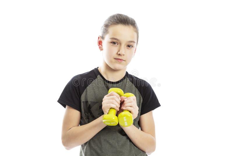 Muchacha adolescente seria con pesas de gimnasia en sus manos Aislado en un fondo blanco imágenes de archivo libres de regalías