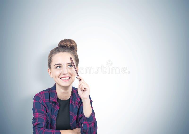 Muchacha adolescente sonriente que piensa, lápiz, gris fotografía de archivo libre de regalías