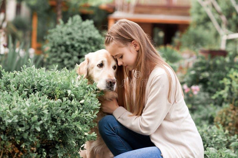 Muchacha adolescente sonriente que presenta con Labrador fotos de archivo