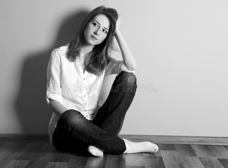 Muchacha adolescente triste en el suelo cerca de la pared. imagen de archivo libre de regalías