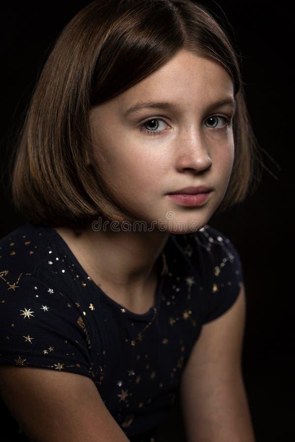 Muchacha adolescente triste hermosa, fondo negro fotos de archivo