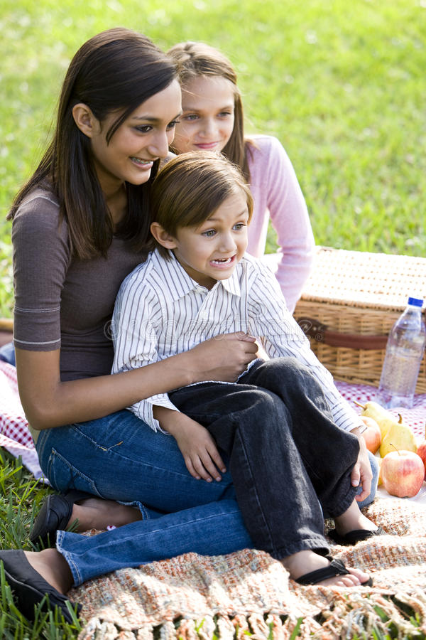 Muchacha adolescente y dos hermanos más jovenes que disfrutan de comida campestre fotografía de archivo libre de regalías