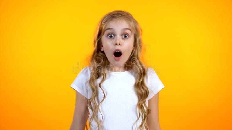 Muchacha adorable con los ojos grandes y la boca abierta que miran a la leva, a las ventas y a los descuentos imágenes de archivo libres de regalías