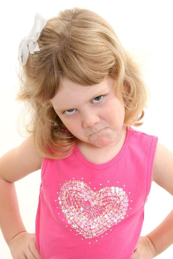 Muchacha adorable de 4 años que pone mala cara con las manos en caderas fotos de archivo