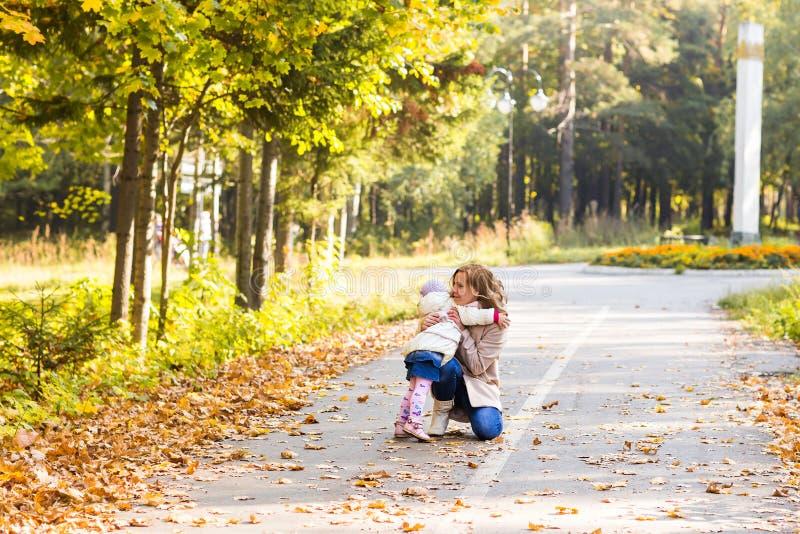 Muchacha adorable del niño y mujer joven en la hija hermosa del bosque del otoño que corre para mimar Retrato de la familia, caíd fotografía de archivo
