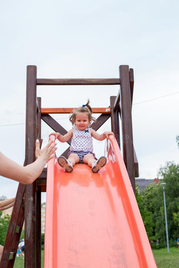 Muchacha adorable en diapositiva en el patio fotografía de archivo