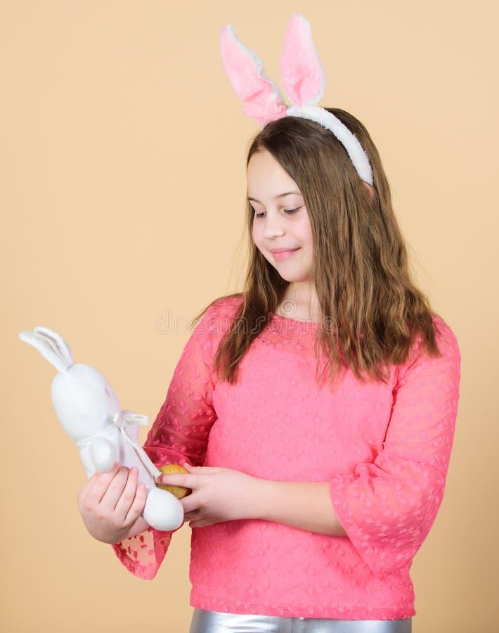 Muchacha adorable en el estilo de Pascua Pequeño niño con el huevo y el conejo coloreados el día de Pascua Poco bebé que sostiene foto de archivo libre de regalías