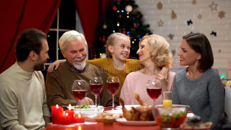 Muchacha adorable feliz que abraza a los abuelos, familia que cena tradicional Navidad fotos de archivo libres de regalías