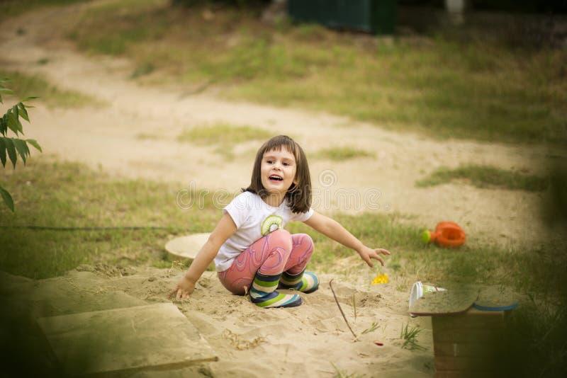 Muchacha adorable que juega con los juguetes en una arena foto de archivo
