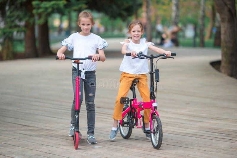 Muchacha adorable que monta una bici en el día de verano hermoso al aire libre imágenes de archivo libres de regalías