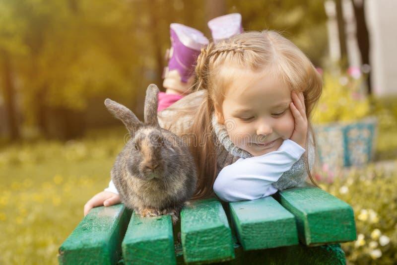 Muchacha adorable que presenta en banco con el conejo lindo foto de archivo
