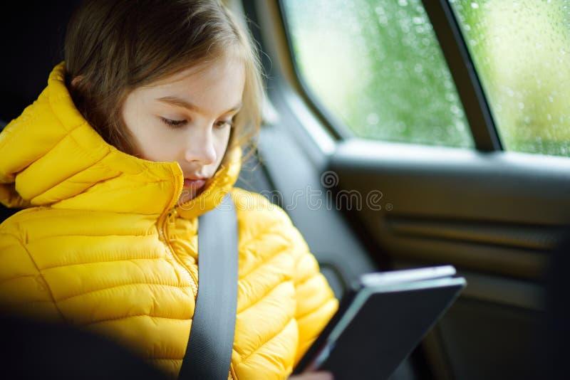 Muchacha adorable que se sienta en un coche y que lee su ebook en día lluvioso del otoño Herserf entretenido del niño en un viaje imagen de archivo libre de regalías