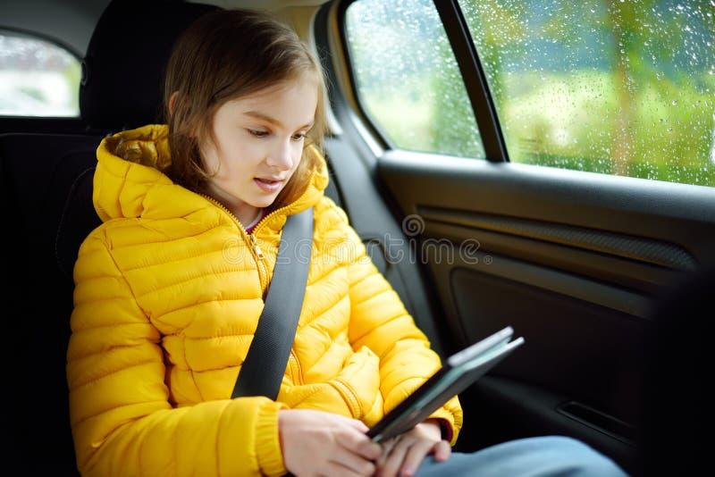 Muchacha adorable que se sienta en un coche y que lee su ebook en día lluvioso del otoño Herserf entretenido del niño en un viaje foto de archivo libre de regalías