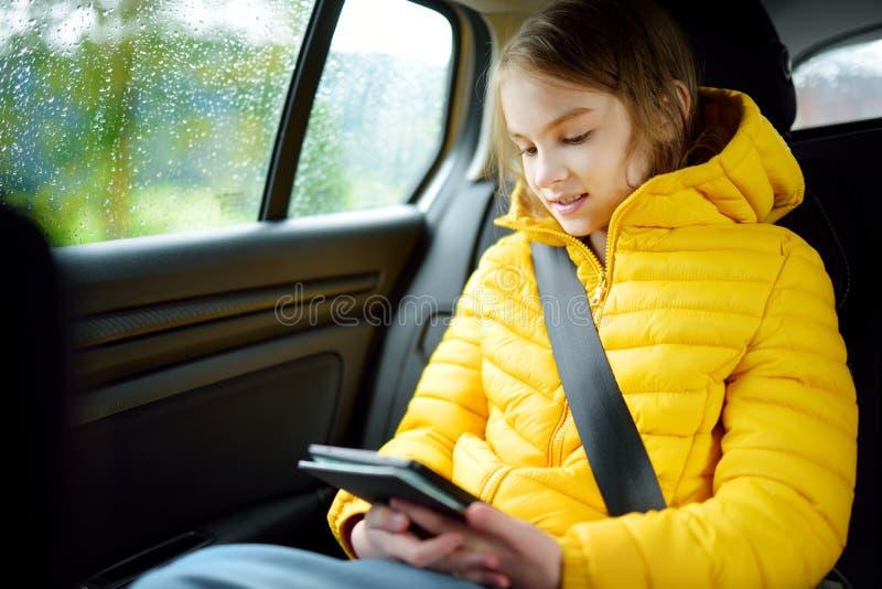 Muchacha adorable que se sienta en un coche y que lee su ebook en día lluvioso del otoño Herserf entretenido del niño en un viaje fotos de archivo libres de regalías