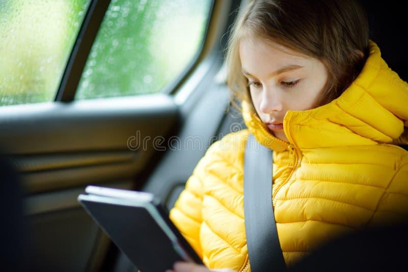 Muchacha adorable que se sienta en un coche y que lee su ebook en día lluvioso del otoño Herserf entretenido del niño en un viaje imagenes de archivo
