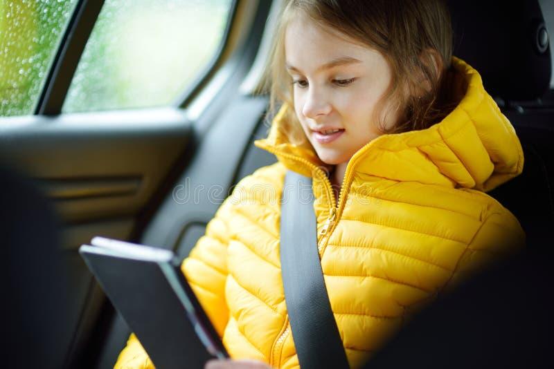 Muchacha adorable que se sienta en un coche y que lee su ebook en día lluvioso del otoño Herserf entretenido del niño en un viaje fotografía de archivo