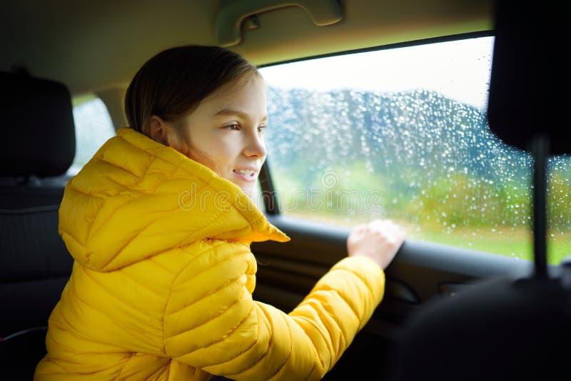 Muchacha adorable que se sienta en un coche y que mira afuera en día lluvioso del otoño Herserf entretenido del niño en un viaje  imagen de archivo
