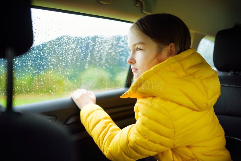 Muchacha adorable que se sienta en un coche y que mira afuera en día lluvioso del otoño Herserf entretenido del niño en un viaje  fotos de archivo
