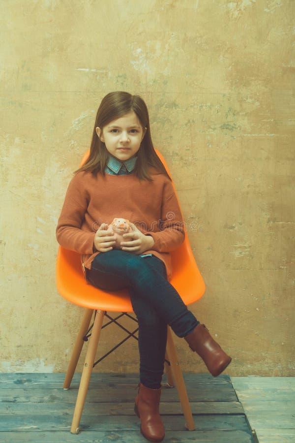 Muchacha adorable que sostiene la hucha rosada imagen de archivo