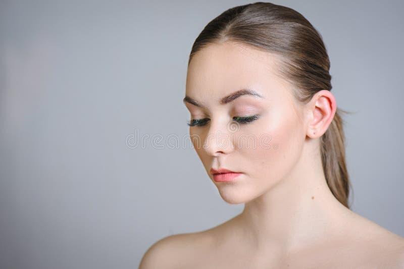Muchacha adulta hermosa que presenta con maquillaje desnudo con la piel limpia y cuidar su piel imagenes de archivo