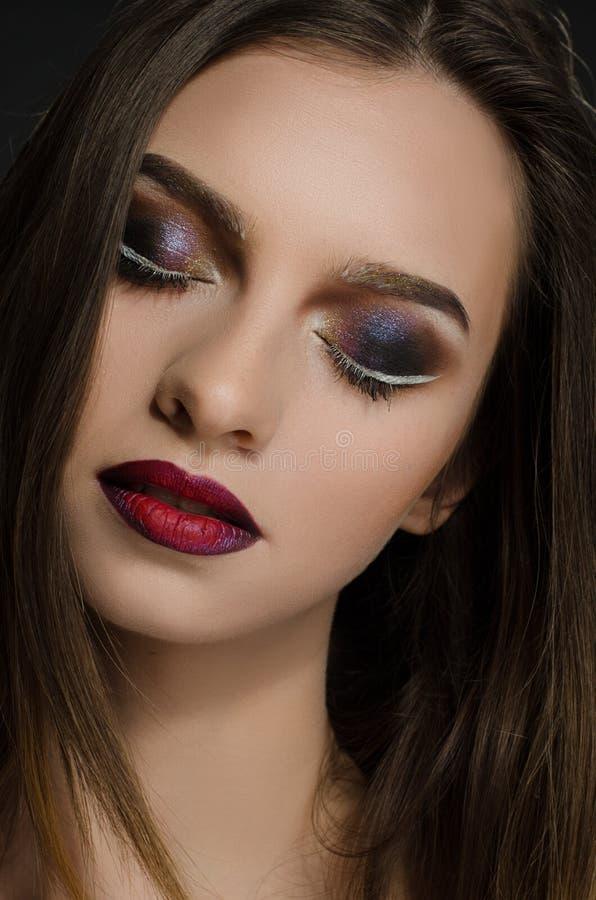 Muchacha adulta joven con maquillaje de igualación hermoso en un fondo negro imágenes de archivo libres de regalías