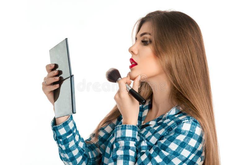 Muchacha adulta joven seria que hace maquillaje en estudio fotografía de archivo libre de regalías