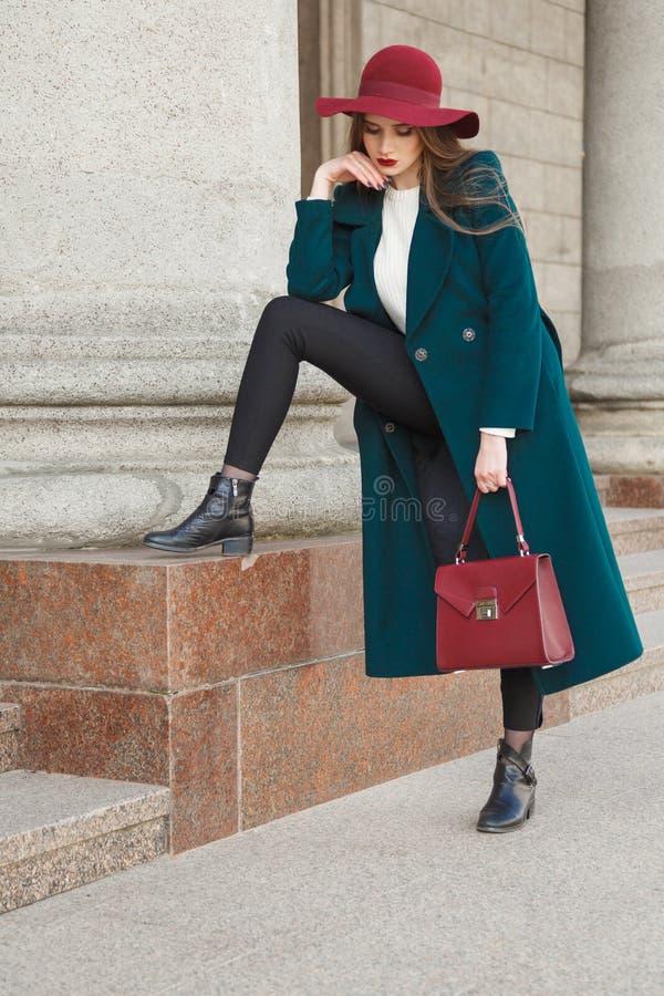 Muchacha afortunada de la moda En sombrero con los campos grandes, la capa caliente larga, un suéter blanco y un ` s de la señora imagen de archivo