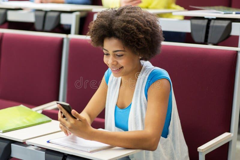Muchacha africana del estudiante con smartphone en conferencia fotografía de archivo