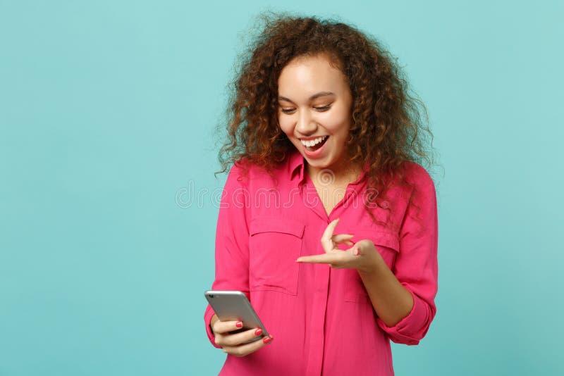 Muchacha africana emocionada en ropa casual rosada usando el teléfono móvil, mensaje del SMS que mecanografía aislado en la pared fotos de archivo libres de regalías