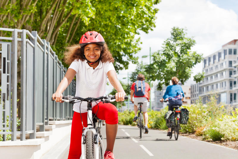 Muchacha africana feliz que completa un ciclo en la trayectoria de la bicicleta en ciudad fotografía de archivo libre de regalías