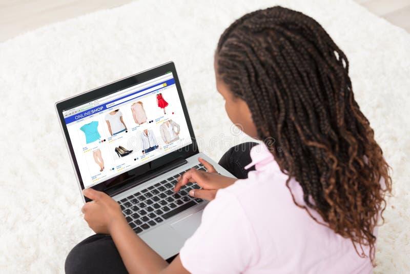 Muchacha africana que hace compras en línea imagen de archivo