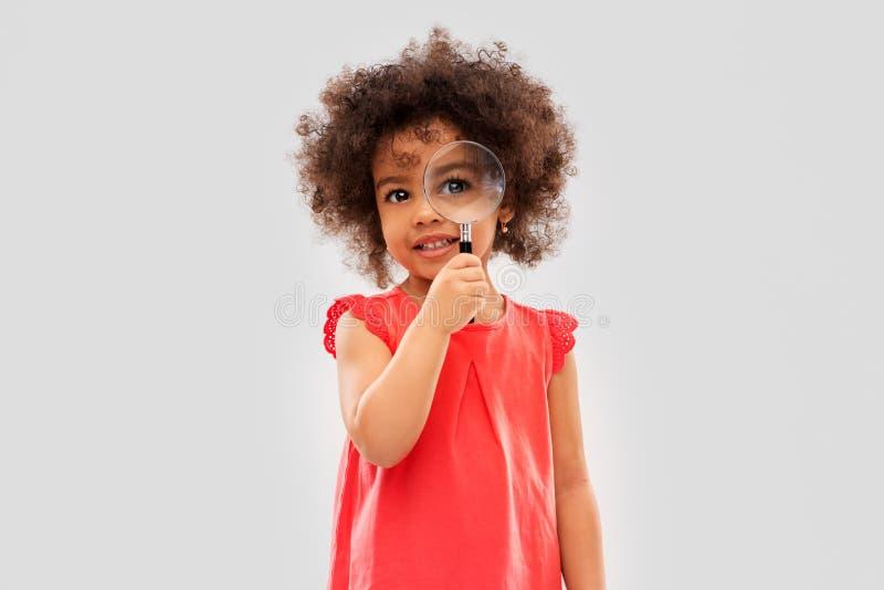 Muchacha africana que mira a trav?s de la lupa fotos de archivo libres de regalías