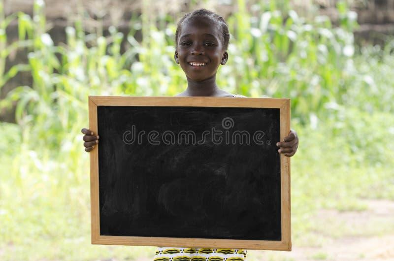 Muchacha africana que presenta al aire libre con una pizarra fotos de archivo