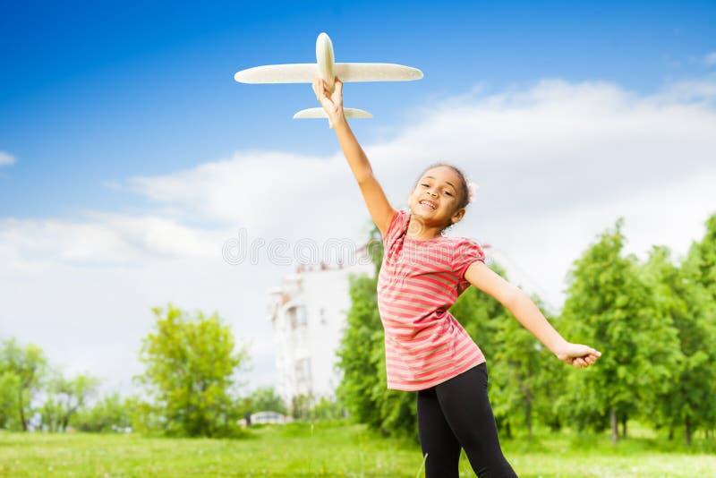 Muchacha africana que sostiene el juguete del aeroplano en campo verde foto de archivo libre de regalías