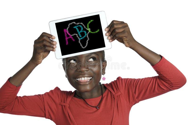 Muchacha africana que sostiene la PC de Minitablet, ejemplo de ABC imagen de archivo libre de regalías