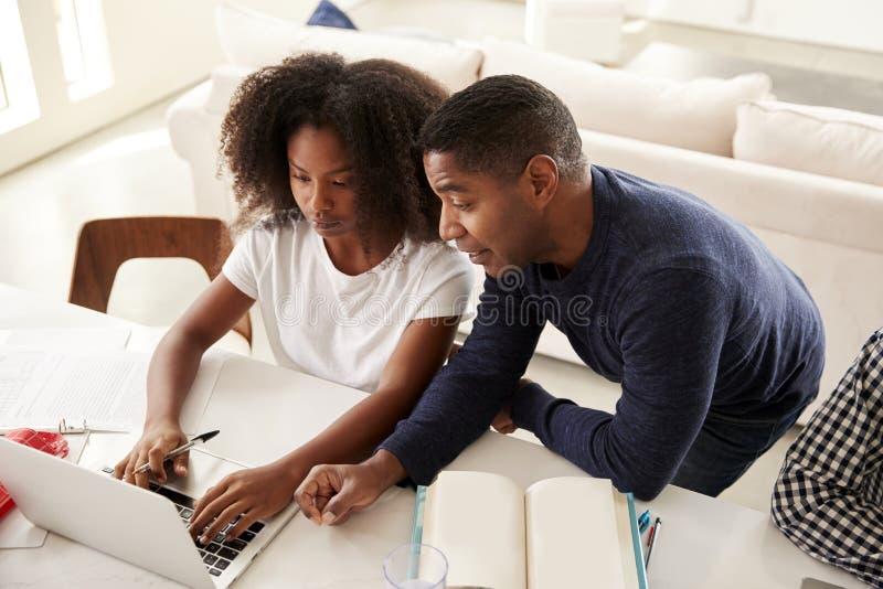 Muchacha afroamericana adolescente que hace la preparación con ayuda de su papá, mirando la pantalla de ordenador, visión elevada fotos de archivo