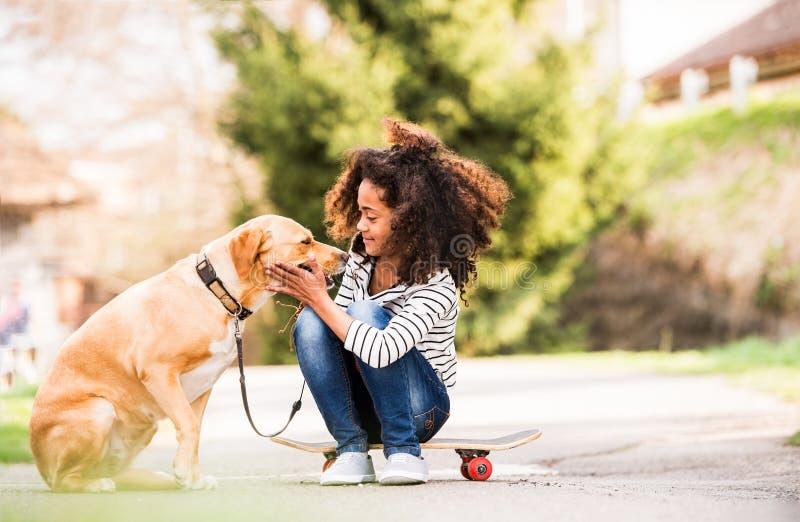 Muchacha afroamericana al aire libre en el monopatín con su perro imagenes de archivo