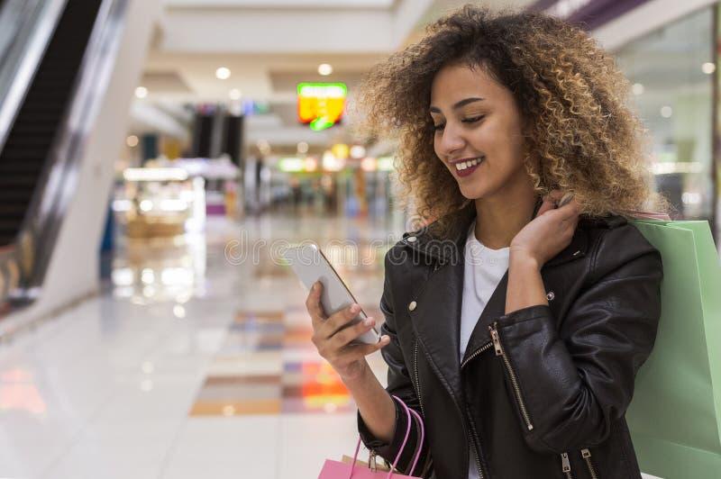 Muchacha afroamericana alegre que tiene charla en el teléfono móvil imagen de archivo libre de regalías