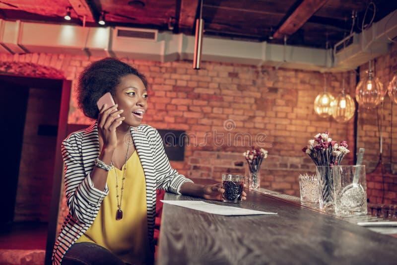 Muchacha afroamericana atractiva brillante del joven-adulto que habla en el teléfono en la barra imagenes de archivo