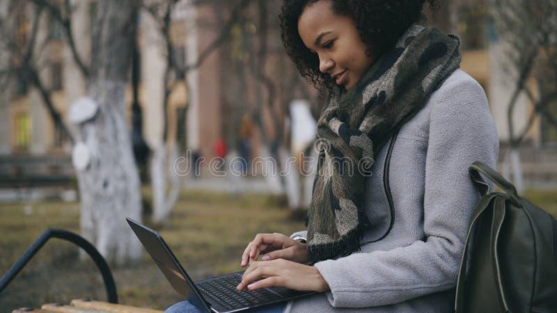 Muchacha afroamericana atractiva del estudiante que mecanografía en el ordenador portátil que se sienta en banco cerca de univerc fotografía de archivo libre de regalías