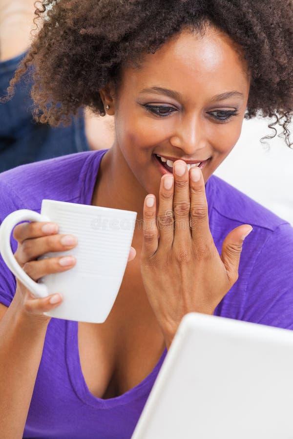 Muchacha afroamericana Biracial que ríe usando el ordenador fotos de archivo libres de regalías