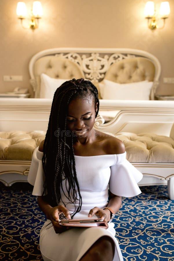 Muchacha afroamericana blanda que se sienta en el piso con la tableta en sus manos delante de la cama grande Blanco que lleva de  fotos de archivo
