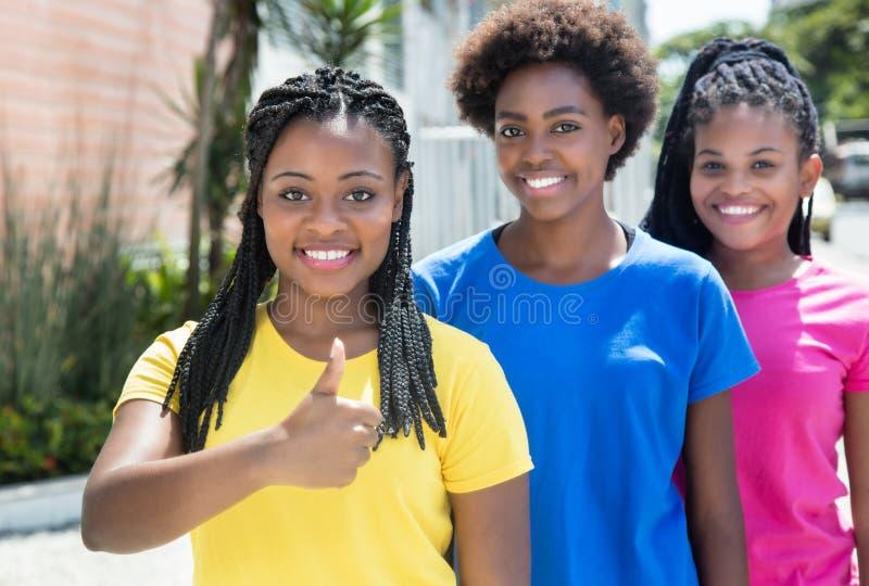Muchacha afroamericana con dos novias que muestran el pulgar fotos de archivo