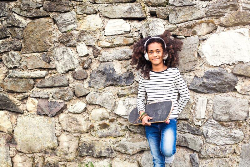 Muchacha afroamericana con el monopatín y los auriculares foto de archivo