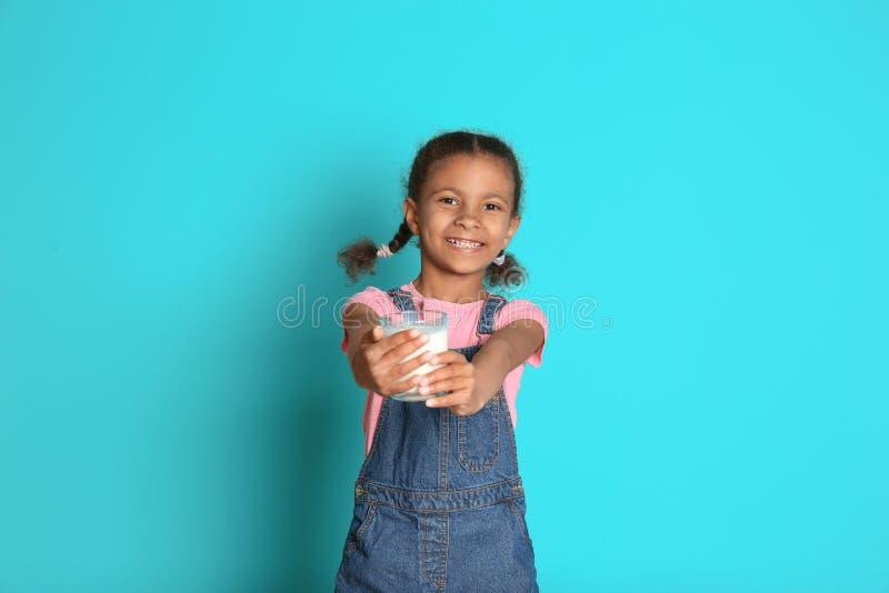 Muchacha afroamericana con el vidrio de leche en fondo del color fotos de archivo