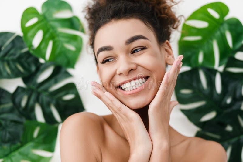 Muchacha afroamericana con la piel perfecta sobre las hojas tropicales fotos de archivo libres de regalías