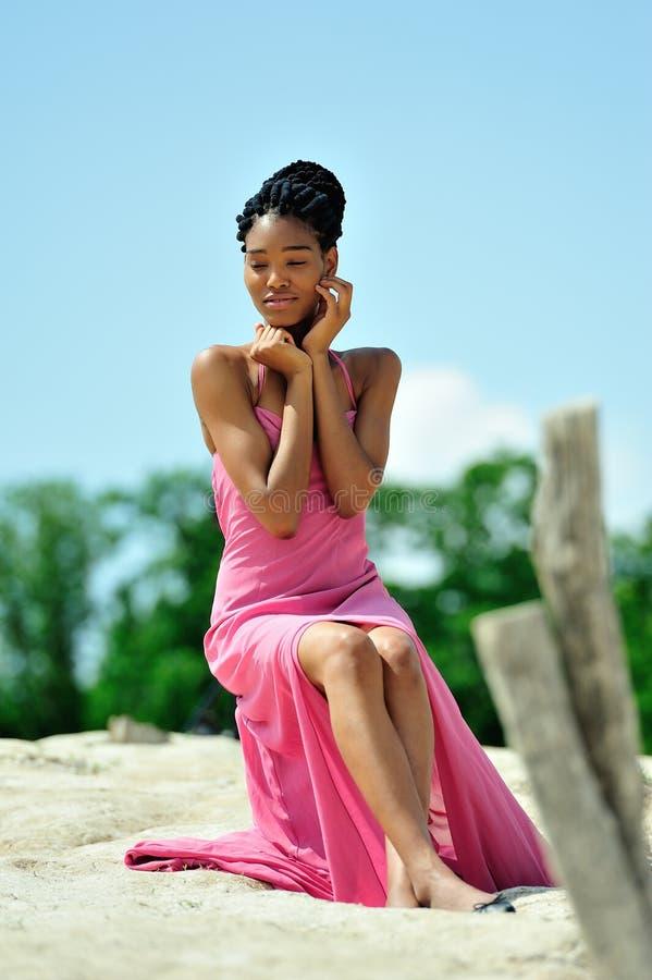 Muchacha afroamericana con los dreadlocks en un vestido rosado que se sienta y que presenta encima de una colina en un día solead foto de archivo