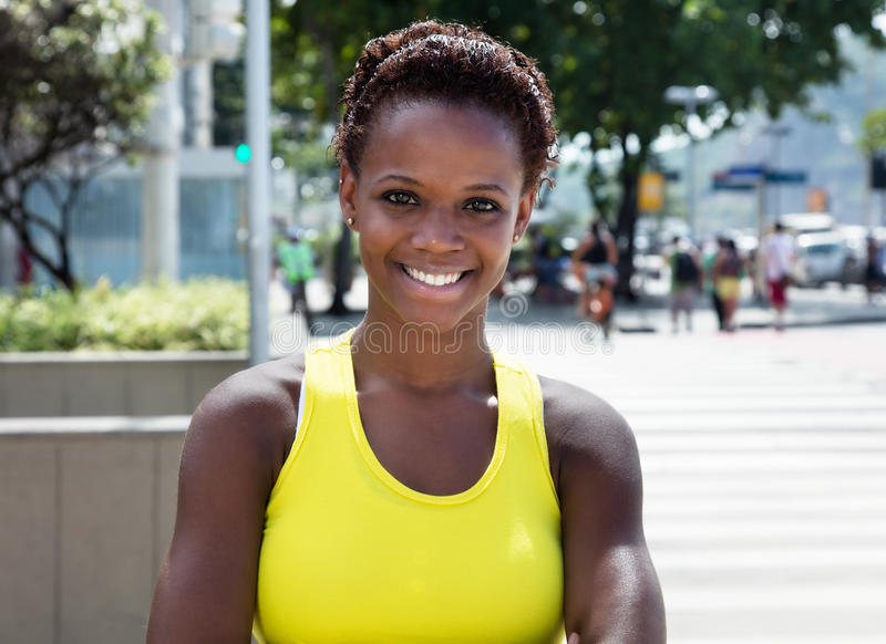 Muchacha afroamericana de risa con la camisa amarilla y el pelo corto imagen de archivo libre de regalías