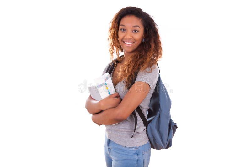 Muchacha afroamericana del estudiante que sostiene los libros - personas negras imagenes de archivo