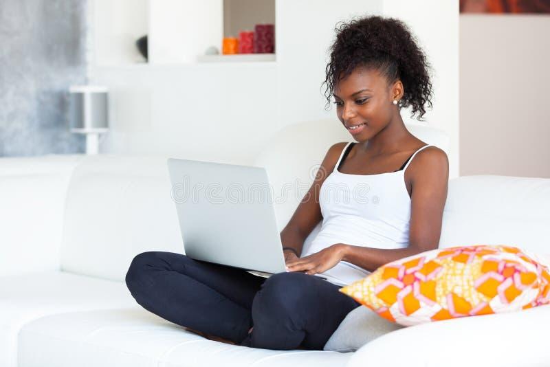 Muchacha afroamericana del estudiante que usa un ordenador portátil - el PE negro fotografía de archivo